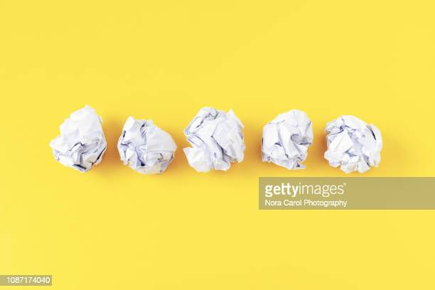 crumpled paper ball on yellow background - mistake stock pictures, royalty-free photos & images