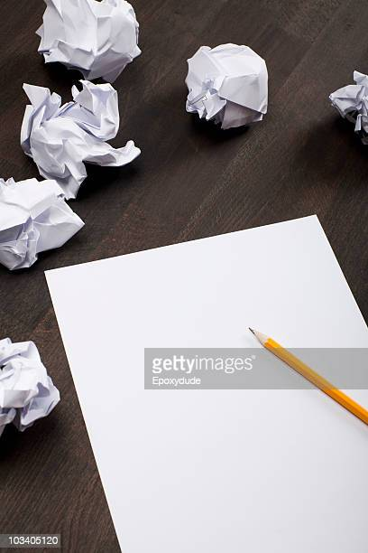 Crumpled paper balls and a blank piece of paper with a pencil