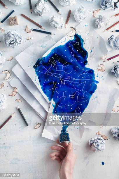 Crumpled paper balls with pencils and papers on a white wooden background with spilled ink forming starry sky with constellations. Writers hand holding an inkwell. Creative writing concept flat lay