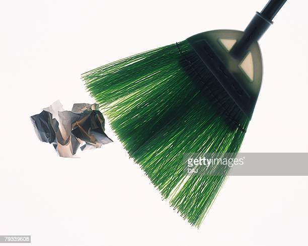 crumpled paper being swept by broom, high angle view, white background - broom sweeping stock pictures, royalty-free photos & images