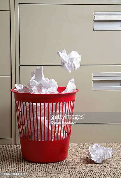 Crumpled paper falling into wastepaper basket