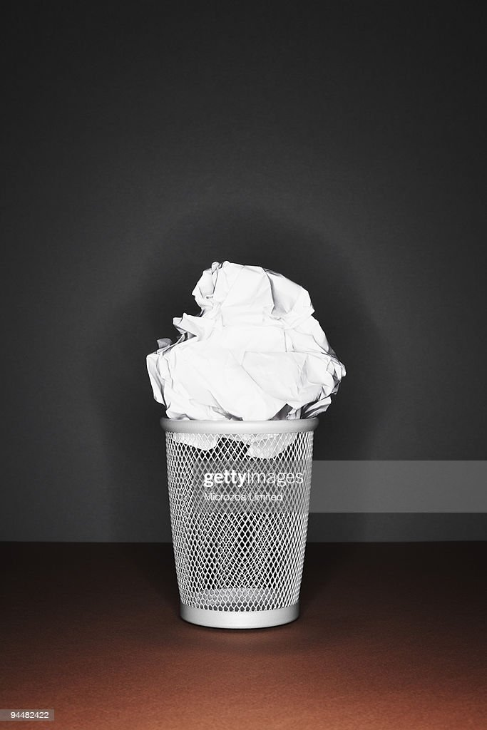 Crumpled paper on top of trash can : Stock Photo
