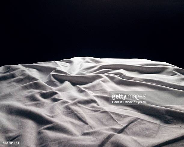 Crumpled Sheet On Bed Against Black Background