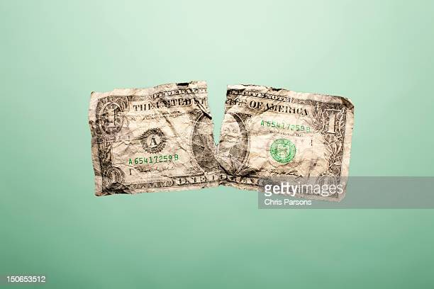 Crumpled up and torn dollar bill