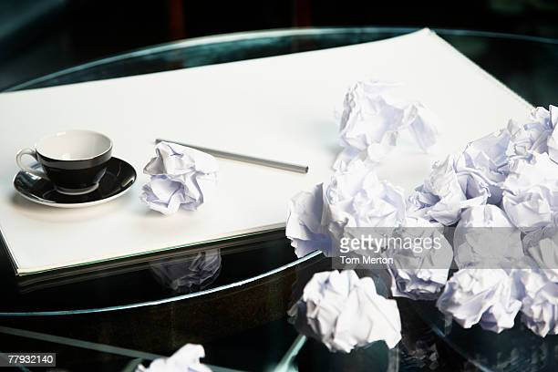 Crumpled up papers on a table by a mug