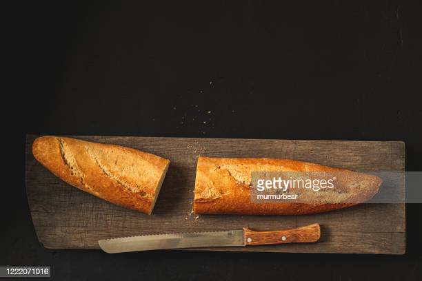 crunchy french baguette and kitchen knife. - baguette stock pictures, royalty-free photos & images
