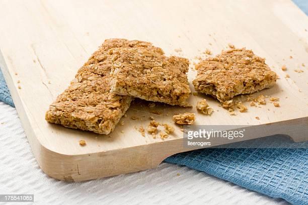 Crunchy oat granola bars served on wooden board