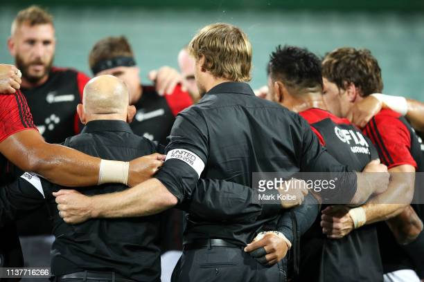 Crusaders coach Scott Robertson is seen during a team huddle wearing a UNITED arm band paying their respects to the victims of the March 15th...