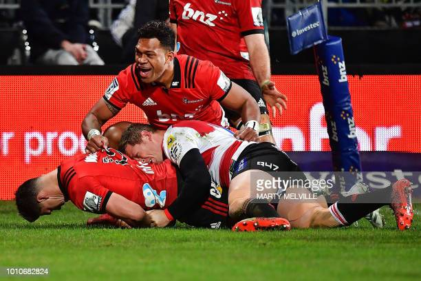 Crusaders' David Havili scores a try as he is tackled by Lions' Ruan Combrinck and teammate Seta Tamanivalu celebrates during the Super Rugby final...
