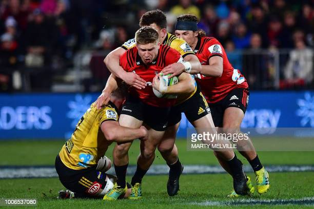 TOPSHOT Crusaders' Jack Goodhue is tackled by Hurricanes' Ricky Riccitelli and Toby Smith during the Super Rugby semifinal match between New...