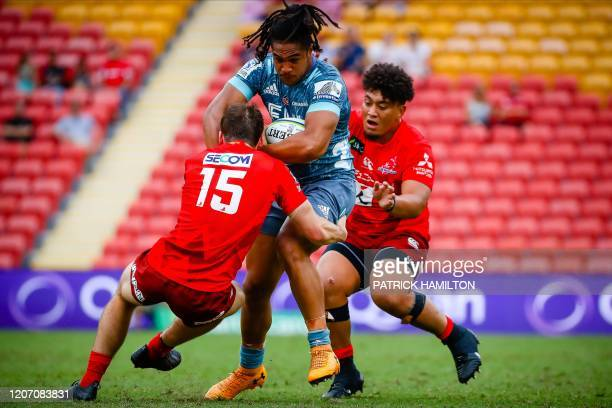 Crusaders' Leicester Faingaanuku breaks the tackle of James Dargaville and Efitusi Maafu of Sunwolves during the Super Rugby match between Japan's...