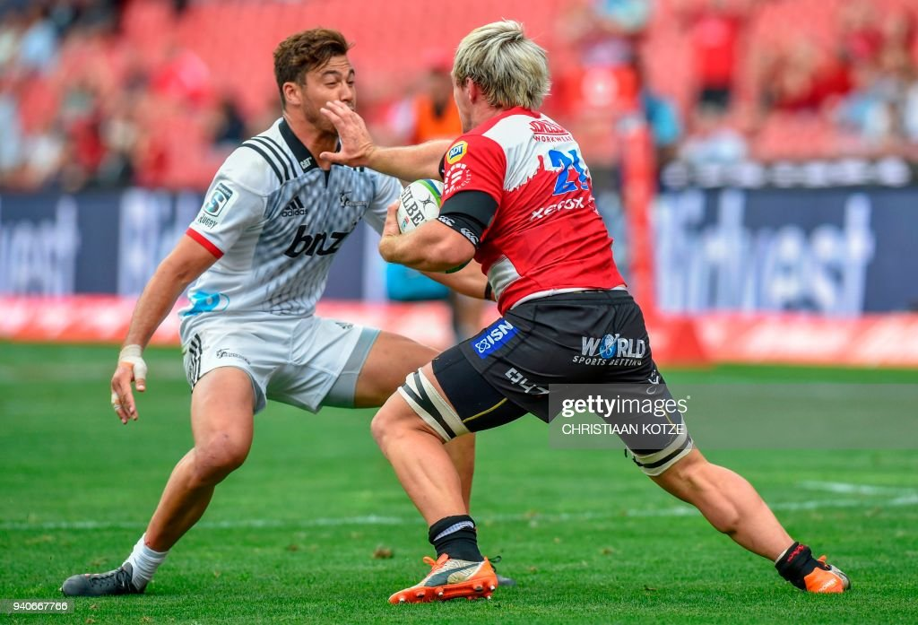 BNZ Crusaders New Zealand midfield David Havili (L) vies with Emirates Lions' South African flanker Marnus Schoeman during the Super Rugby XV match Emirates Lions versus BNZ Crusaders on April 1, 2018 at the Emirates Airline Park in Johannesburg. / AFP PHOTO / Christiaan Kotze