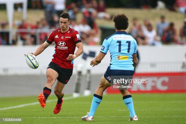 Crusaders Player Will Jordan kicks over the head of Waratahs wing Mark Nawaqanitawase during the Round 1 Super Rugby match between the Crusaders and...