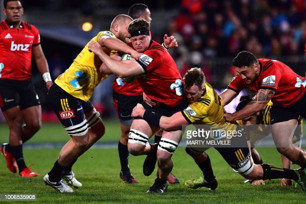 TOPSHOT Crusaders' Scott Barrett is tackled by Hurricanes' captain Brad Shields and Gareth Evans during the Super Rugby semifinal match between New...