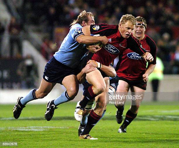Crusaders Scott Hamilton attempts to run from Waratahs Phil Waugh in the final of the Super 12 rugby at Jade Stadium Christchurch New Zealand...