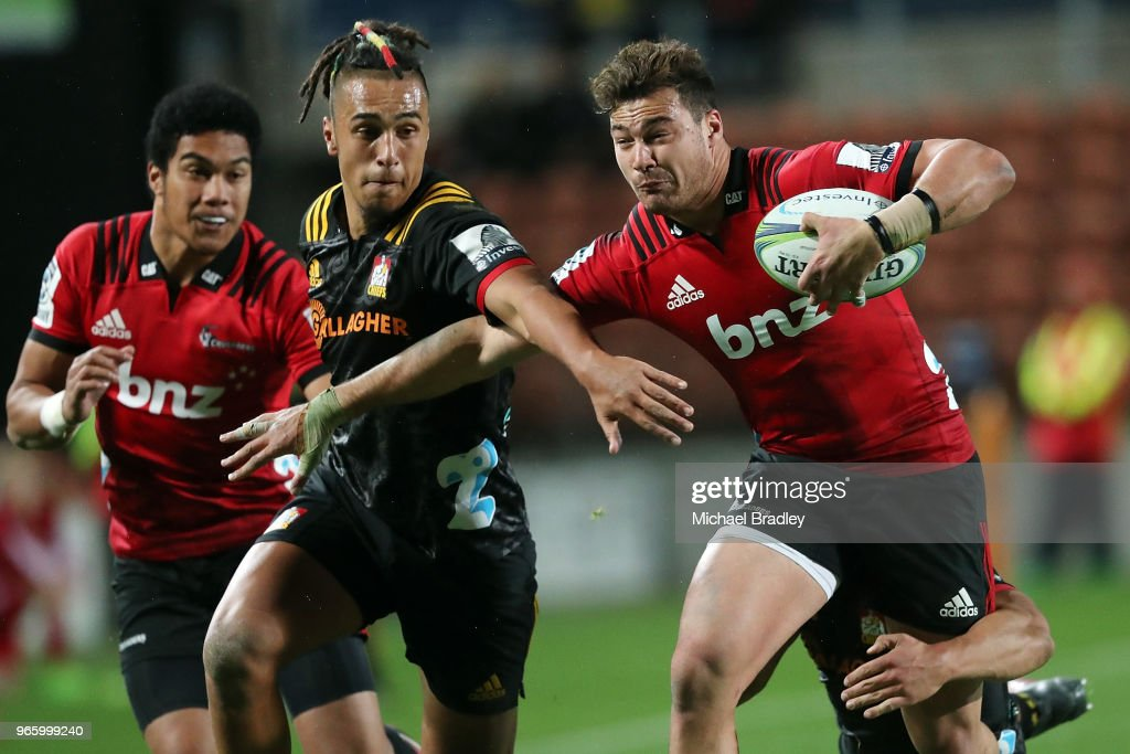 Crusaders second five David Havili is tackled by Chiefs winger Sean Wainui (C) and Anton Lienert-Brown (R) during the round 16 Super Rugby match between the Chiefs and the Crusaders at Waikato Stadium on June 2, 2018 in Hamilton, New Zealand.
