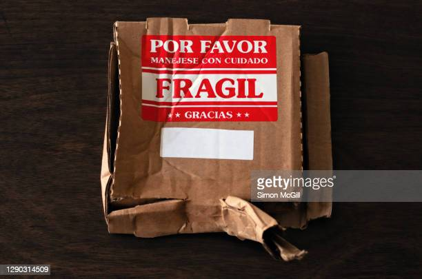 crushed cardboard box parcel with a spanish-language fragile: handle with care label - fragile sticker stock pictures, royalty-free photos & images