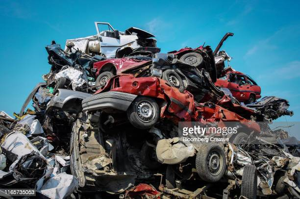 crushed cars at a vehicle scrapyard - obsolete stock pictures, royalty-free photos & images