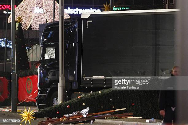 A crushed Christmas tree lays on the ground beside debris after a lorry truck was ploughed through a Christmas market on December 19 2016 in Berlin...