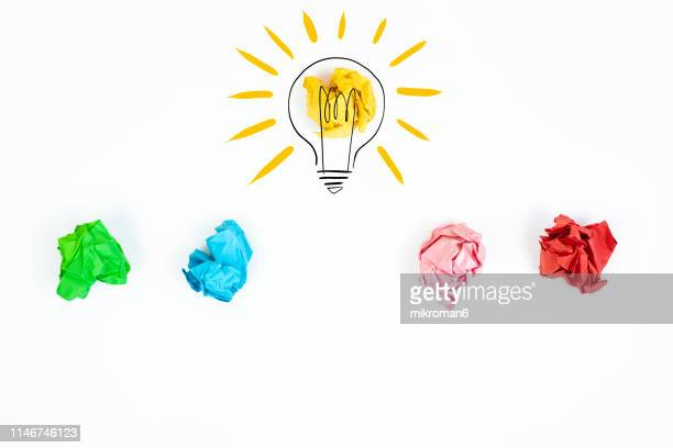 crushed pages  of paper and a light bulb - ideas stock pictures, royalty-free photos & images