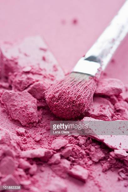 Crushed pink eye shadow and a make-up brush