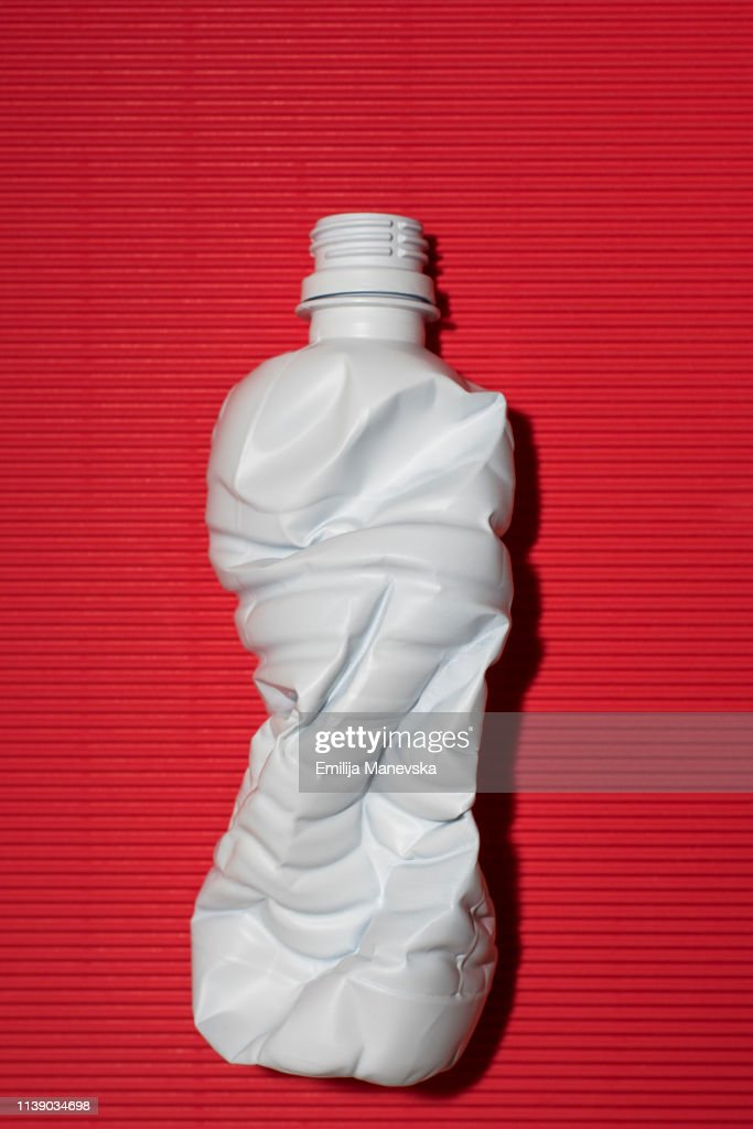 Crushed plastic bottle on colored background : Stock Photo