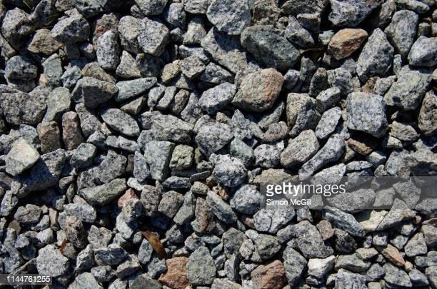 crushed quartz granite rocks spread on the ground - 砂利 ストックフォトと画像
