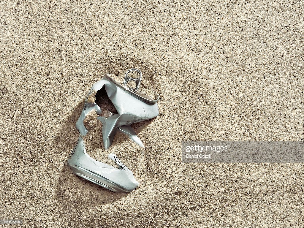 crushed tin can buried in sand : Stock Photo