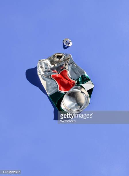 crushed tin can on purple background - tin can stock pictures, royalty-free photos & images