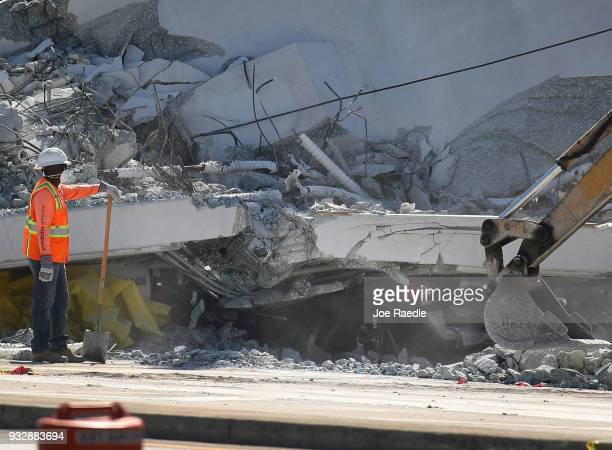 A crushed vehicle is seen near a worker as law enforcement and members of the National Transportation Safety Board investigate the scene where a...
