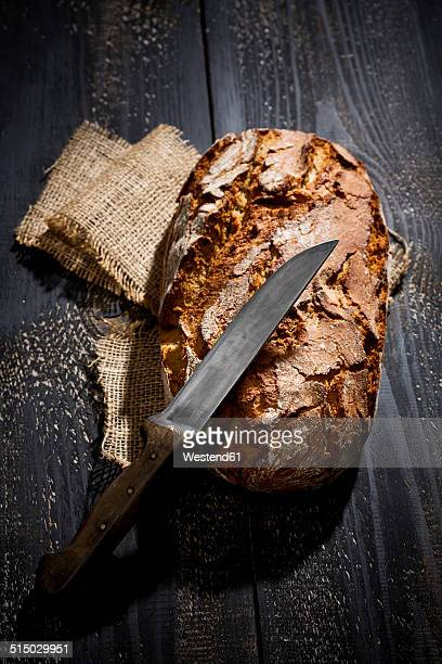 Crusty bread and knife on jute in front of dark background, elevated view