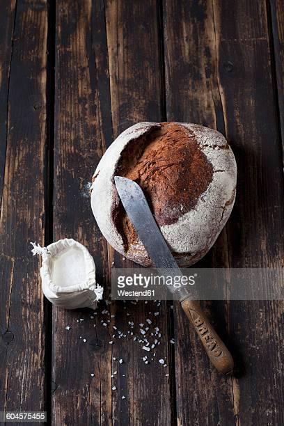 Crusty bread, bread knife and sachet of salt grains on dark wood
