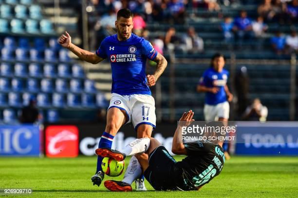 Cruz Azul's Edgar Mendez vies for the ball with Miguel Samudio of Queretaro during their Mexican Clausura 2018 tournament football match at the Azul...