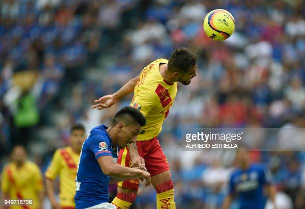 Cruz Azul's player Angel Mena jumps for the ball with Morelia's Mario Osuna during their 2018 Mexican Clausura tournament football match at Azul...