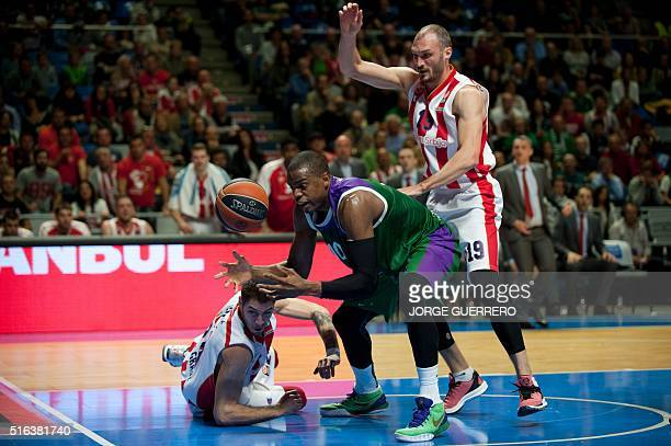 Crvena Zvezda Telekom Belgrade's guard Stefan Jovic and forward Marko Simonovic vie with Unicaja's Georgian forward Will Thomas during the Euroleague...