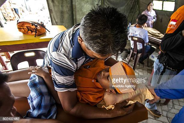 Crying boy is comforted by a family member as he is being circumcised during a charge-free mass circumcision provided for the refugee of mount...