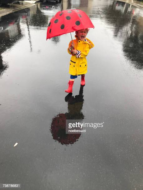 Crying boy wearing a raincoat and wellington boots standing in the rain with an umbrella, Orange County, California, America, USA