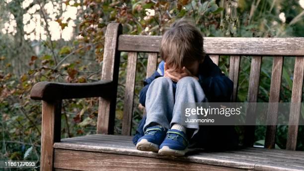 schreeuwende kindjongenzitting op een bank die zijn gezicht behandelt - lagere schoolleeftijd stockfoto's en -beelden