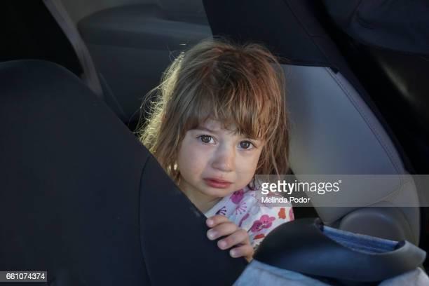 Crying child inside a mini van, looking at camera