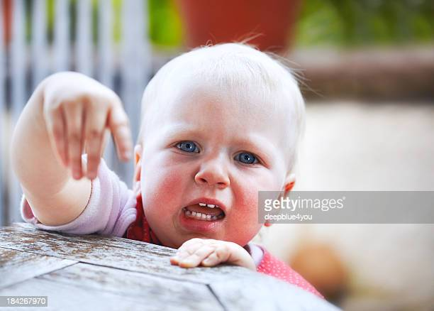 Crying little child standing on table pointing with finger