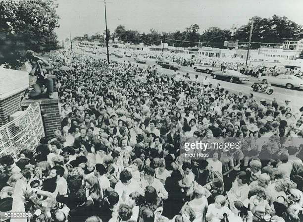 Crying pushing and fainting more than 10000 mourners try to force their way into Graceland mansion to view body of rock' n' roll star Elvis Presley