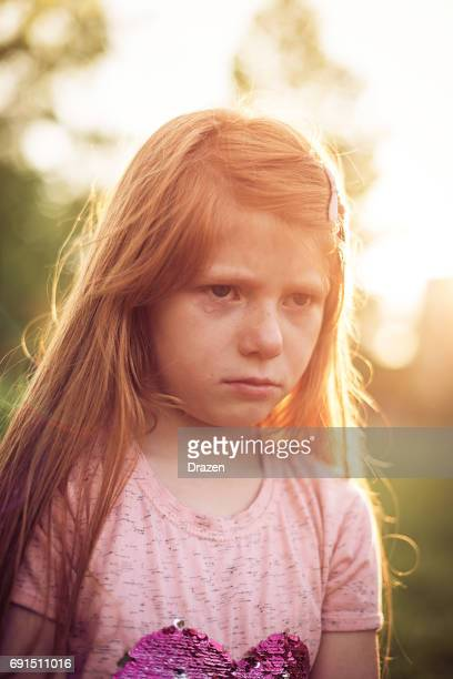 Crying redhead girl in park expressing disappointment and anger
