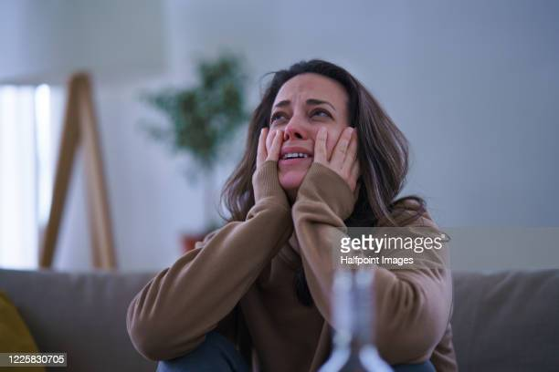 crying sad and depressed woman sitting indoors on sofa. - crying stock pictures, royalty-free photos & images