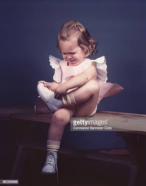 Crying toddler girl tying her shoes