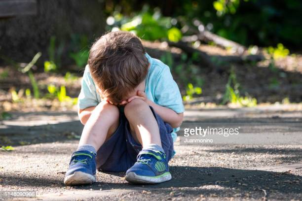 crying toddler sitting on the floor covering his face - orphan stock pictures, royalty-free photos & images