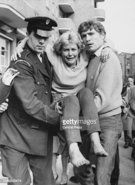 Crying woman is carried by two men to an ambulance after she was injured during the St Pancras rent riots, with local authority housing block...