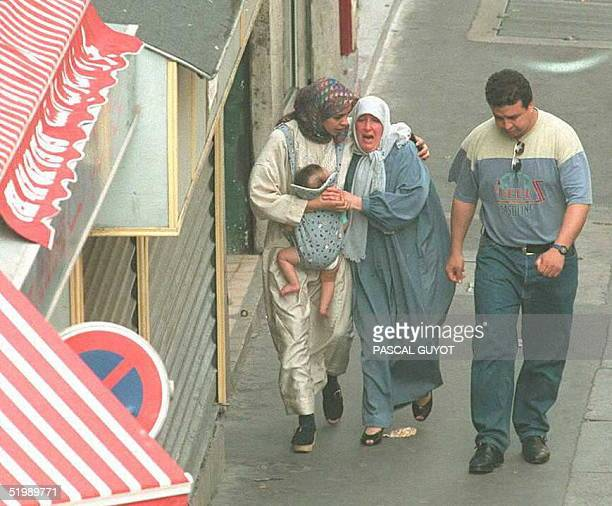 A crying woman is helped by a friend 11 July as she leaves a mosque in northern Paris where cofounder of the Algerian fundamentalist group the...
