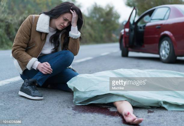 crying woman kneeling next to injured man on the road - dead bodies in car accident photos stock photos and pictures