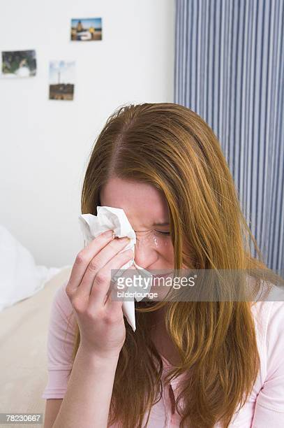 crying woman rubbing her eyes with tissue