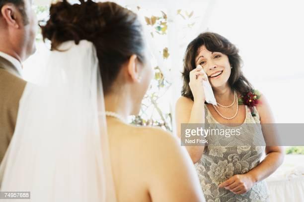 Crying woman watching bride walk down aisle